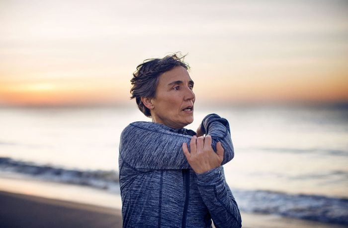 Mujer estirandose en la playa antes de hacer ejercicio y conocer el rol del colágeno en la salud